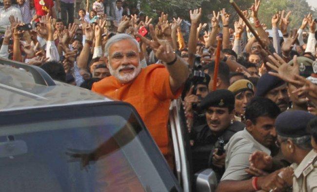 Gujarat state Chief Minister Narendra Modi, center, greets his supporters...