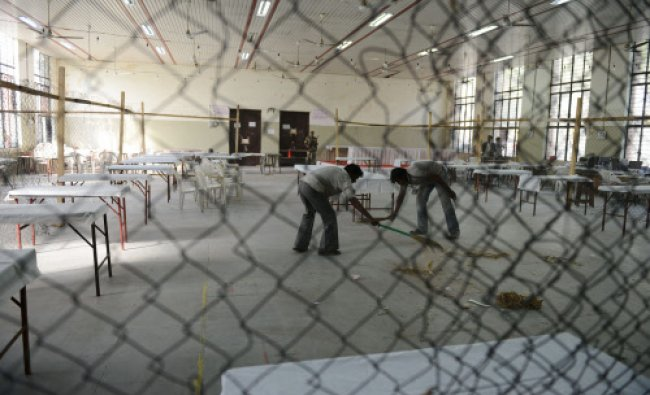 Workers clean the hall where the counting of votes...
