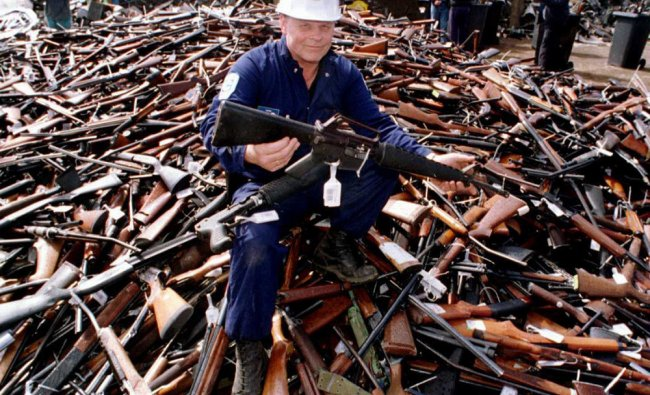 Norm Legg, a project supervisor with a local security firm, holding up an armalite rifle
