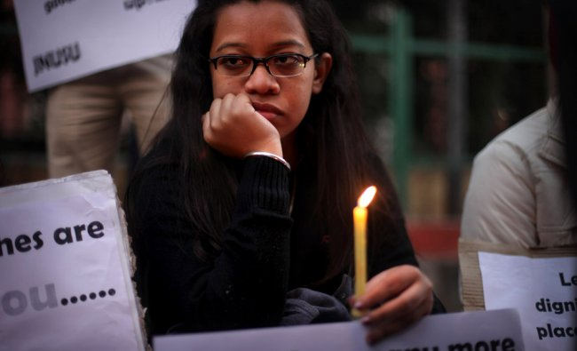An Indian woman watches as she participates in a candlelight vigil outside the hospital...