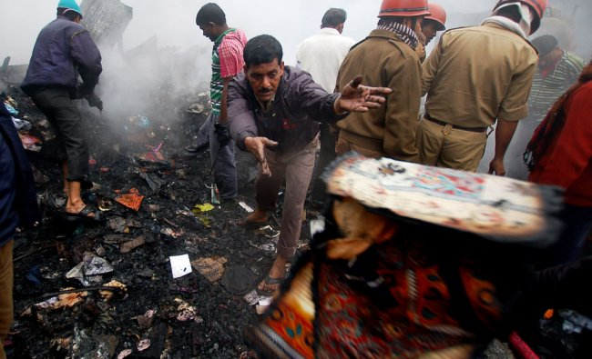 Indian firefighters trying to control a fire that broke out at garment shop at a supermarket...