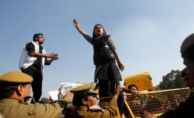 A demonstrator standing on a barricade erected by police shouts slogans during a protest rally...