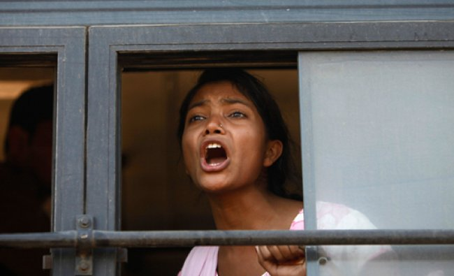 A demonstrator shouts slogans from inside a bus after she was detained by police near...