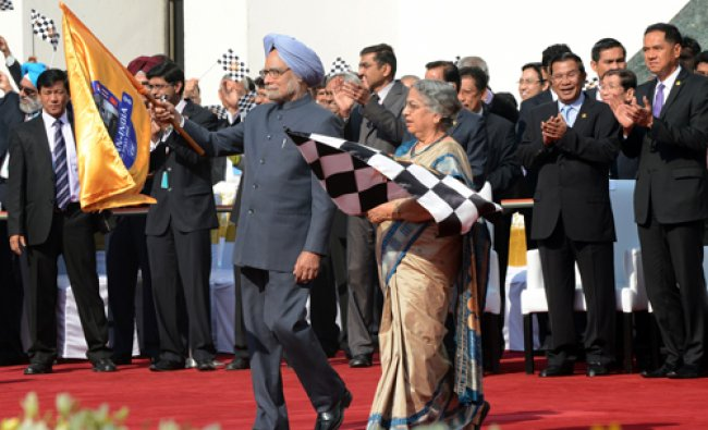 Indian Prime Minister Manmohan Singh and his wife Gulcharan Kaur hold a flag during the ASEAN...