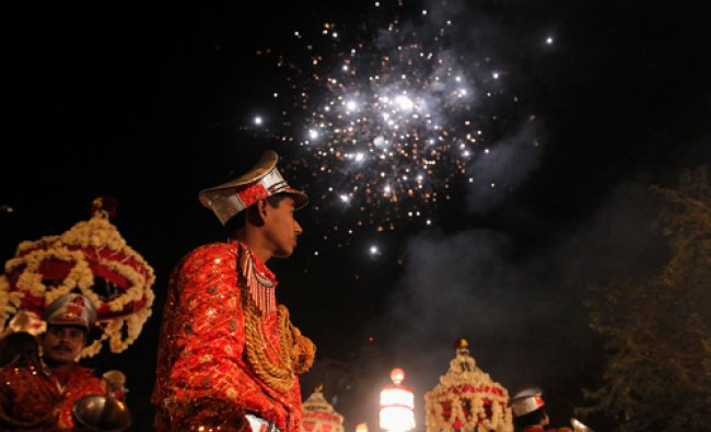 Members of the brass band play as fireworks are set off during a wedding procession in Noida...