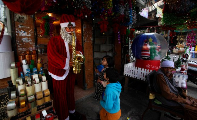 Children look at a Santa Claus figure outside a christmas decoration shop in Lahore...