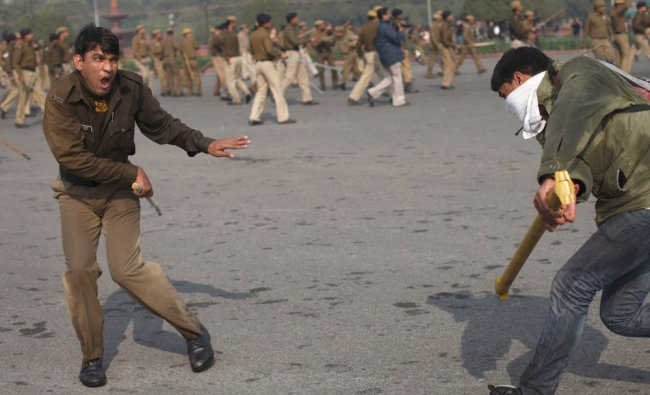 A student tries to hit a policeman with an iron rod during a protest in New Delhi...
