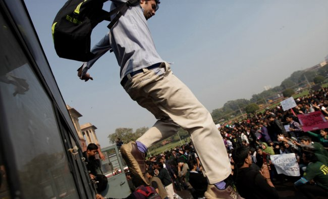 A student jumps from inside a police bus after he was detained during a protest in Delhi...