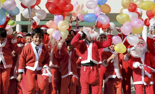 Children dressed as Santa Claus take part in the Christmas celebrations in Bhopal ...