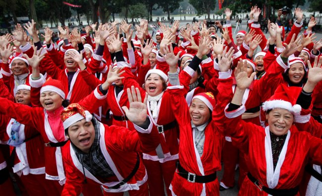 Members of the Laughter Yoga club in Santa Claus costumes practise laughing during a morning exercis
