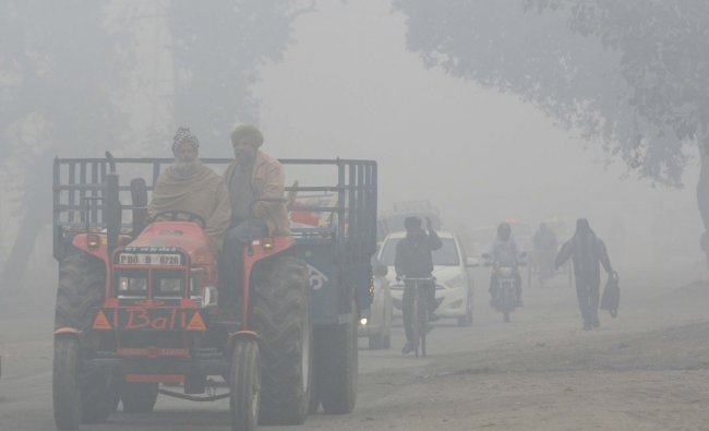 Commuters make their way through thick fog along a road in Amritsar on December 23, 2012...