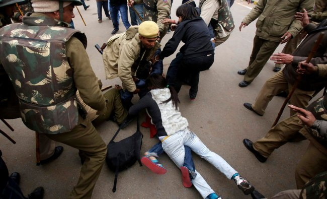 Police detain demonstrators near the India Gate during a protest in New Delhi...