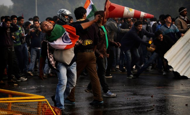 Protester throws a traffic cone at Indian police during a violent demonstration near the India Gate
