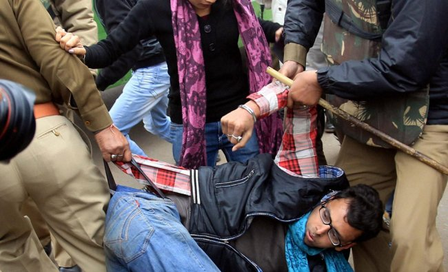 Police detain one of the protesters at Raj Path in New Delhi on Sunday
