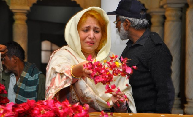 A Pakistan People\'s Party (PPP) member scatters rose petals on the grave of assassinated former...