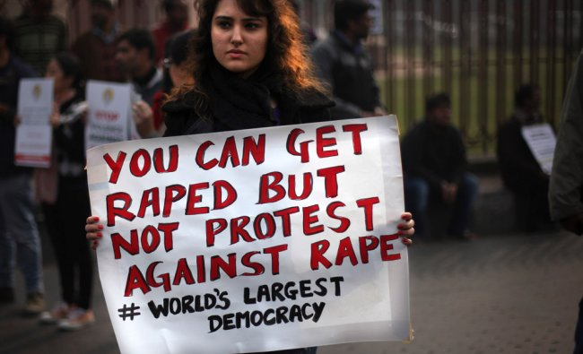 A protester holds a placard during a protest against a recent gang rape of a young woman