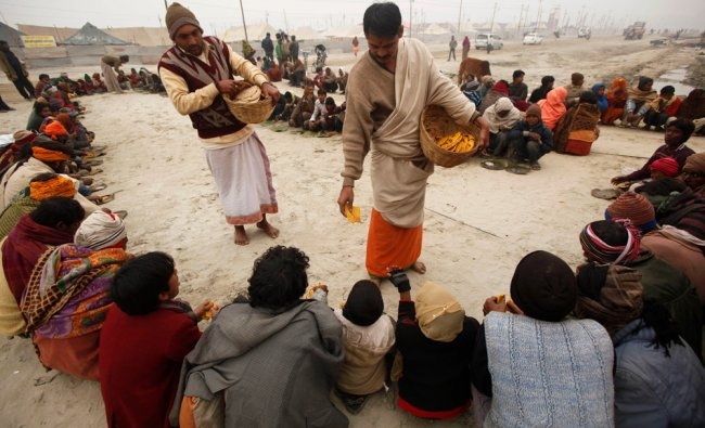 People eat a free meal during the preparations for the month-long Mahakumbh festival at Sangam