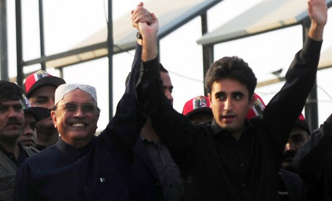 Asif Ali Zardari waves with his Bilawal Bhutto to supporters outside the Bhutto family mausoleum