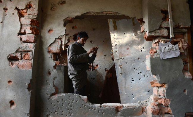 A Kashmiri Muslim looks at a damaged house where Indian troops killed two militants belonging to LeT
