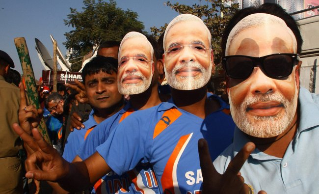 Cricket fans wear masks of Gujarat Chief Minister Narendra Modi and stand in a queue