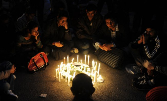 Protesters sit in silence around candles during...