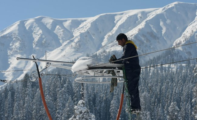 A Kashmiri electrician adjusts an electric wire in Gulmarg...