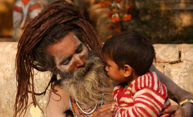 A Sadhu speaks with a young boy beside a tent at Allahabad
