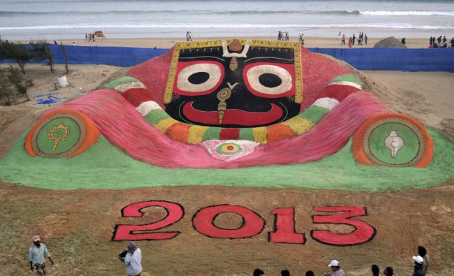 Visitors look at a sand sculpture designed to celebrate the 2013 new year...