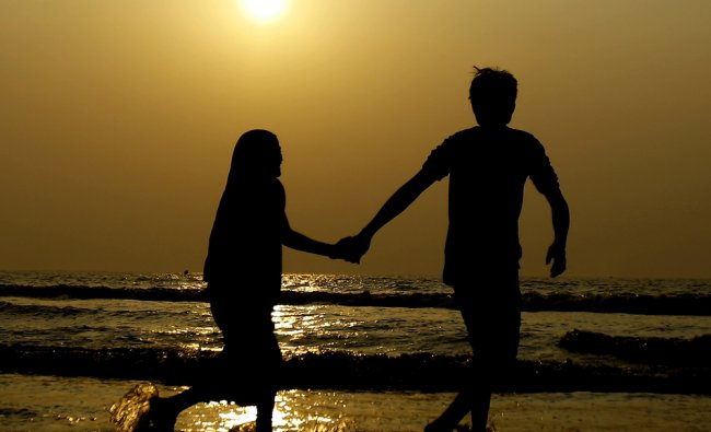 A Couple stands as they watch the last sunset of 2012 over the shores of the Arabian sea