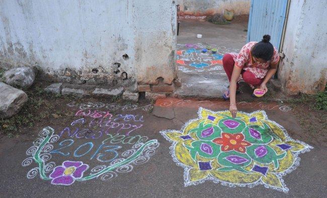 A woman applies coloured powder to her \'rangoli\'...