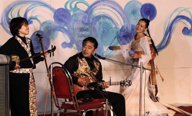 Members of the Japanese folk fusion band \'Kariyushi\', perform, as painter Saori Kanda, right...