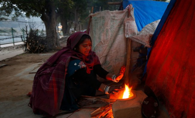 A woman warms herself by a fire to to stay warm in New Delhi...