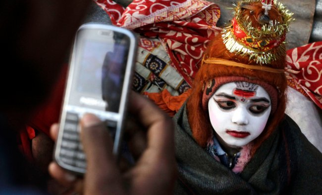 A young Indian boy dressed as Hindu god Shiva begs for alms