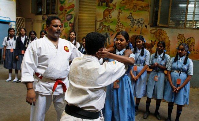 School girls watch martial art experts demonstrate self defense