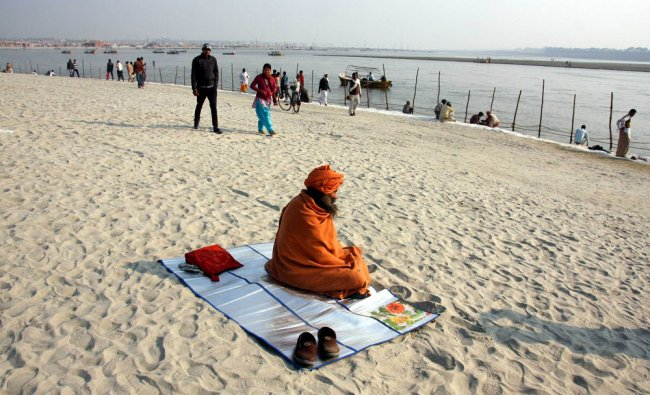 An Indian Hindu Dadhu (holy man) sits in the sun following last week\'s cold spell across the region.
