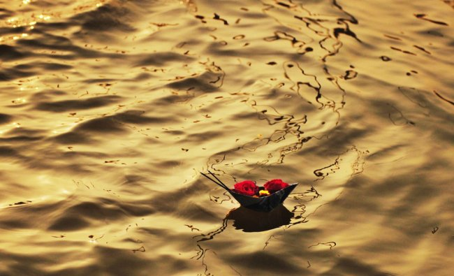 A candle burns on an offering floating down stream at the Sangham or confluence of the Yamuna....
