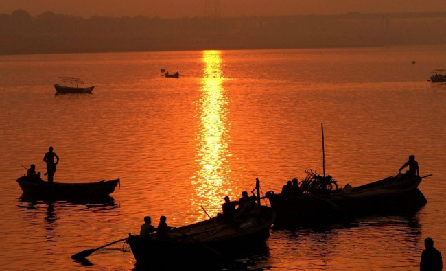 Hindu devotees travel in boats during sunset at sangam in Allahabad on Sunday. PTI Photo
