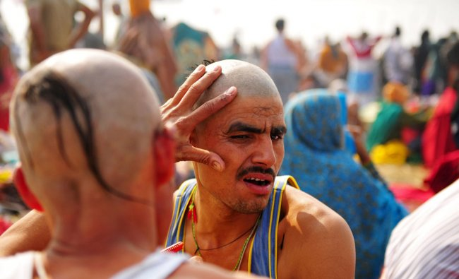 A Devotee gets his head shaven before taking a dip in the Sangham at the Kumbh Mela celebration...