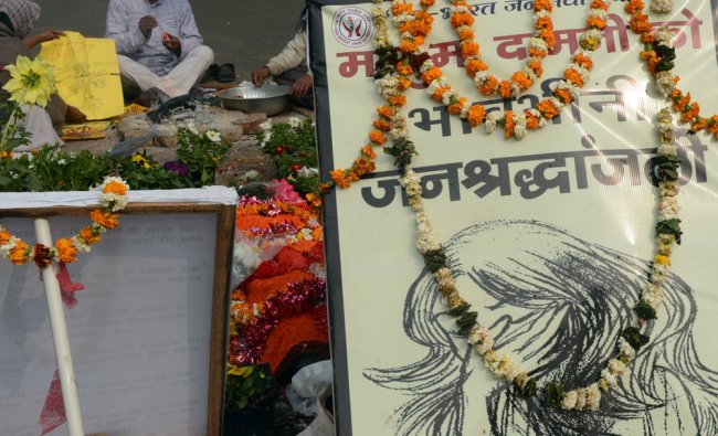 Demonstrators pray at a memorial during the one-month anniversary of the gang rape in New Delhi...