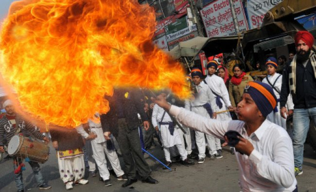 A young Sikh blows flames during a procession to celebrate the birth anniversary...