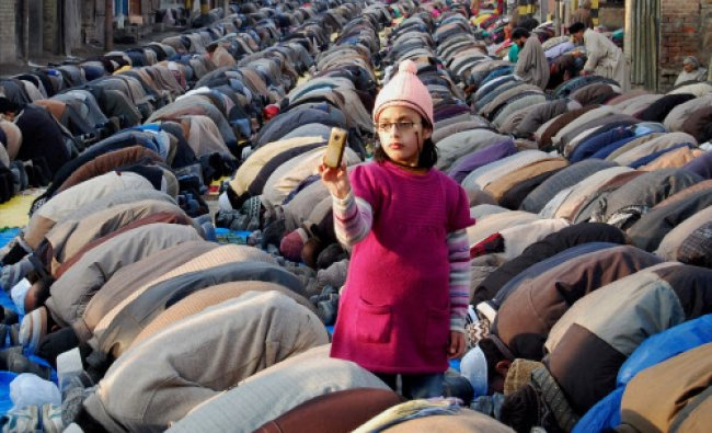 A Muslim girl takes picture on mobile as her elders offer special prayers...