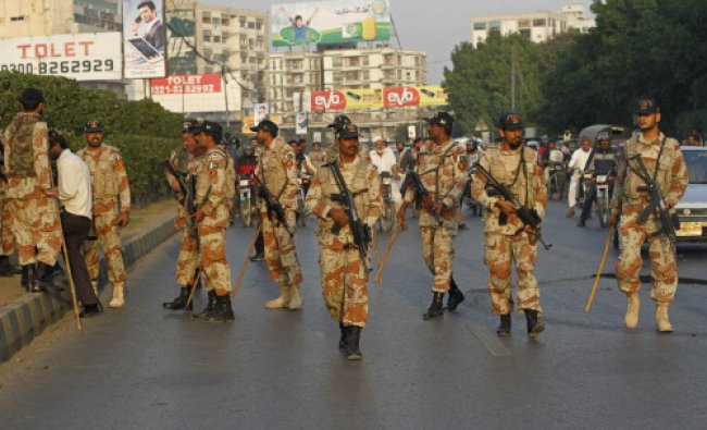 Paramilitary soldiers hold weapons as they walk to restore traffic after a protest of PPP