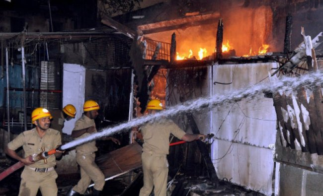 Fire personnel dousing a fire that broke out in a Phool Bazar in Hubli