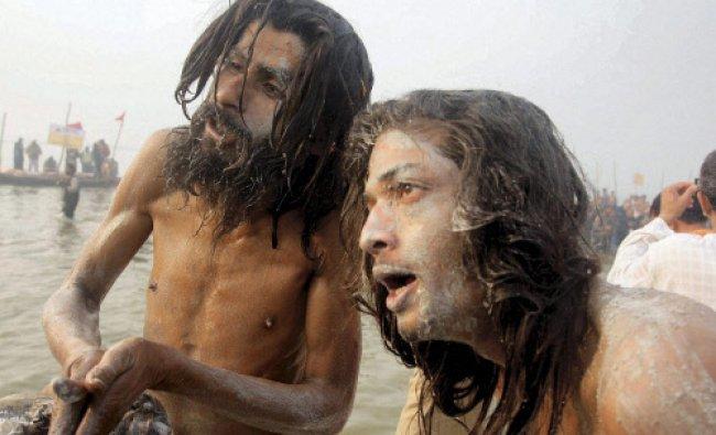 Naga Sadhus apply ashes on thier faces after taking bath at Sangam