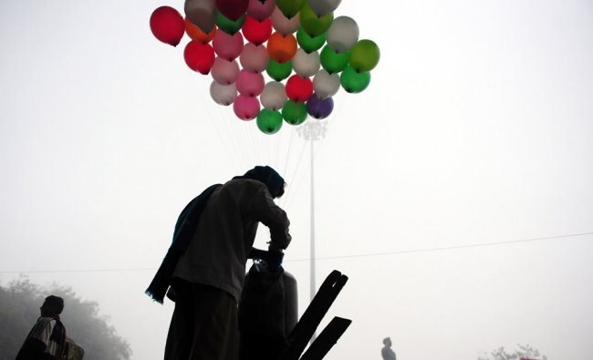 An Indian vendor inflates balloons during a foggy and cold morning in Allahabad....