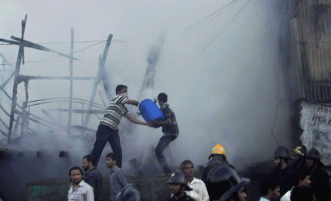 Fire personnel and residents douse a fire that broke out at Azad Nagar in Mumbai