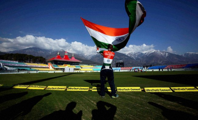 A supporter of Indian cricket team waving a Tricolor as the players practise in Dharamshala....