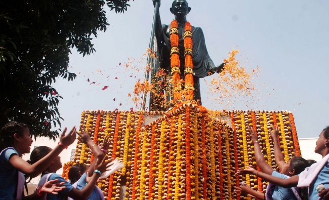 School children pay homage at a memorial statue of Mahatma Gandhi on his 65th death anniversary...