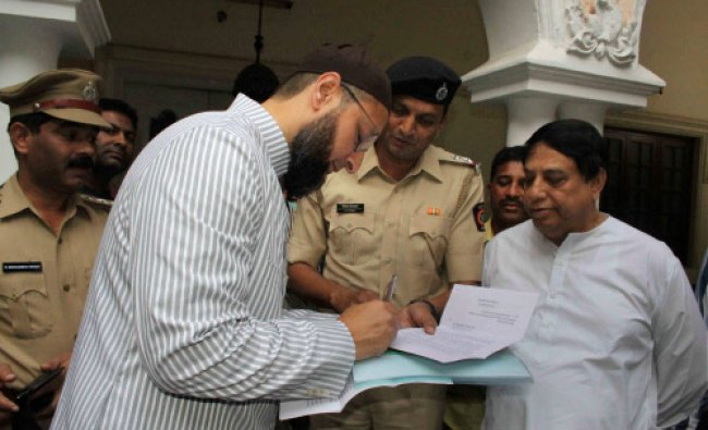 Asaduddain Owaisi signs on a notice at his residence