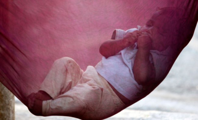 An Indian child sleeps nestled in a cloth hammock on a street in Mumbai, India, Wednesday...